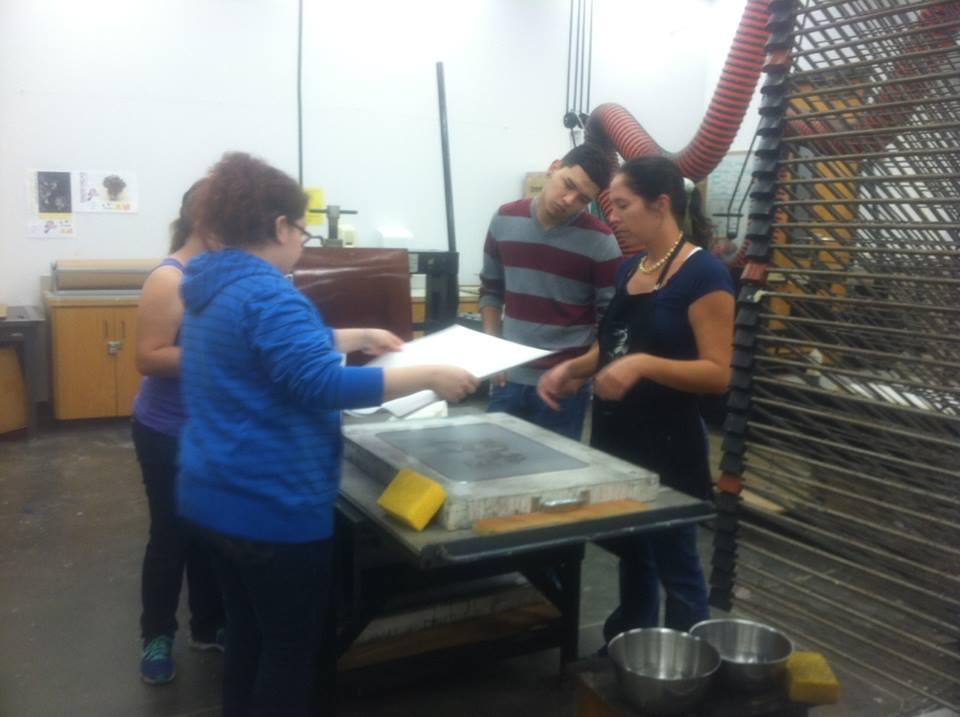 Estudiantes de arte que ayudan a Laura a imprimir la litografía