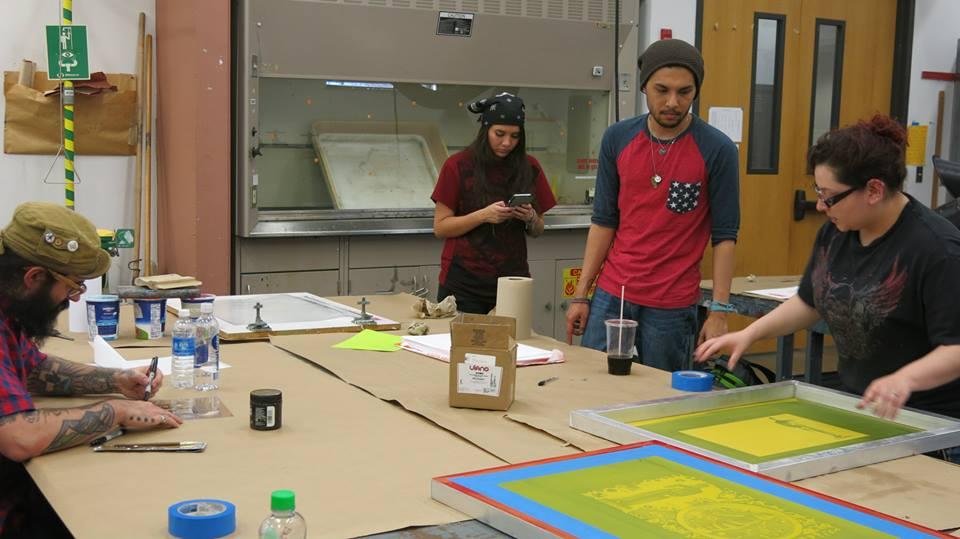 Los estudiantes de arte Cynna, Ricardo y Andrea preparan una pantalla