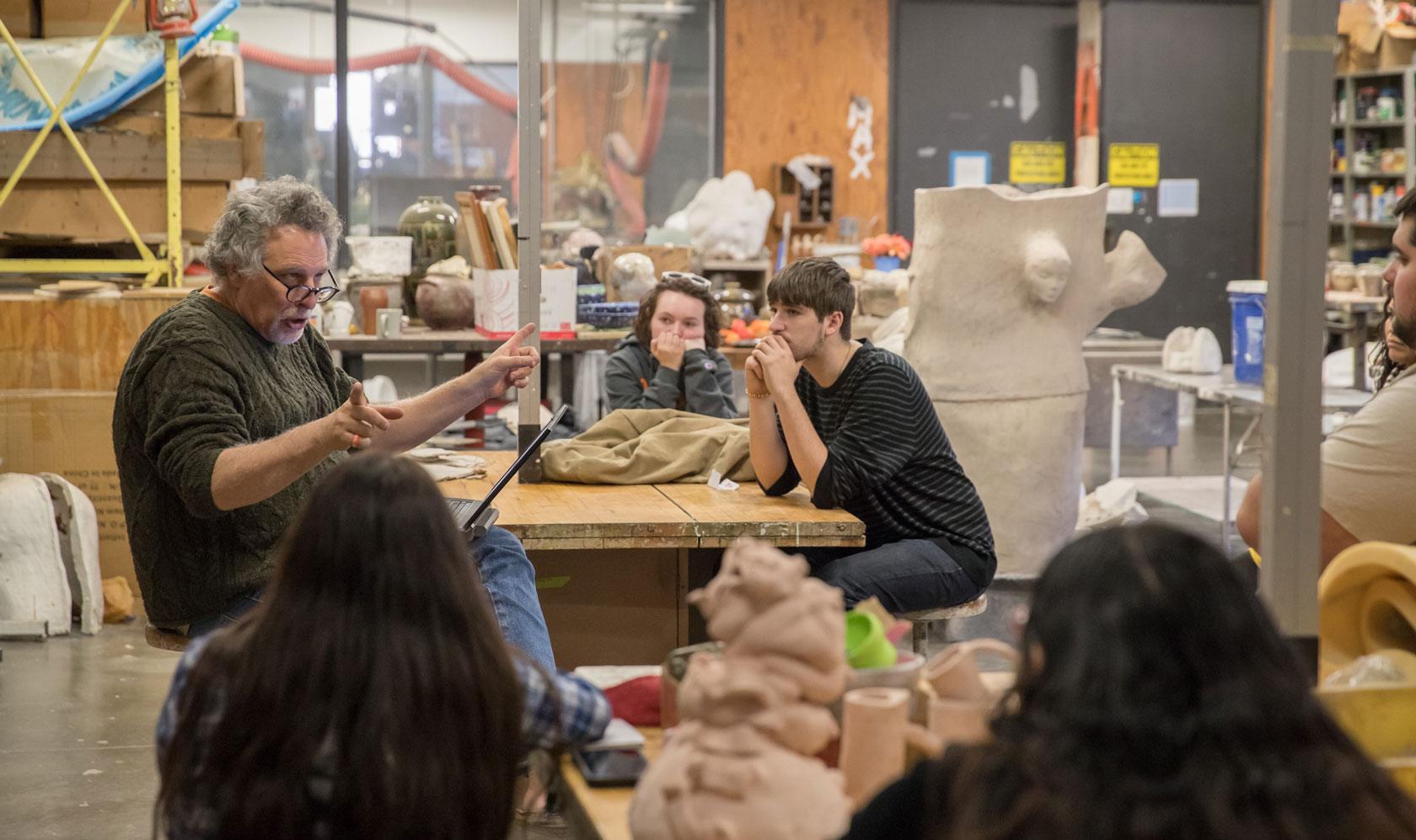 Profesor de arte discutiendo sobre cerámica