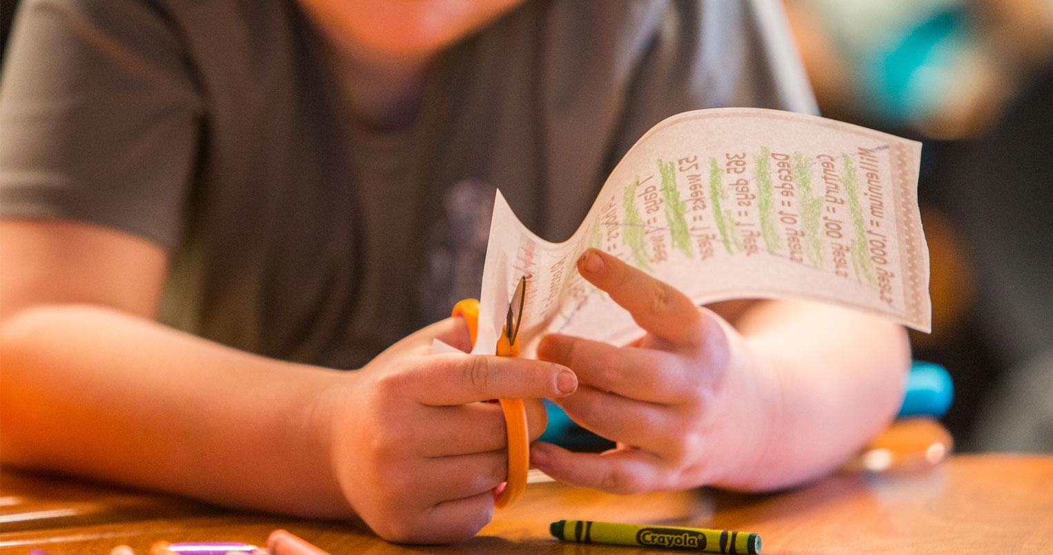 estudiante cortando papel