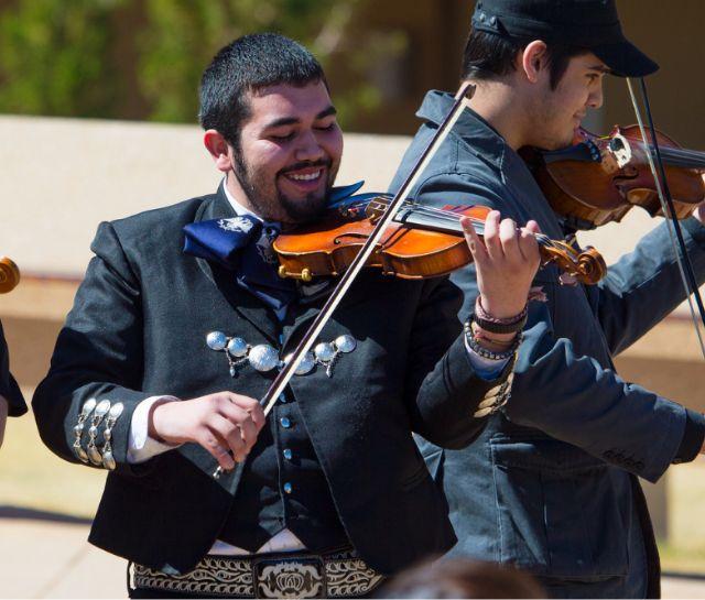 Estudiante varón en banda de mariachis tocando el violín