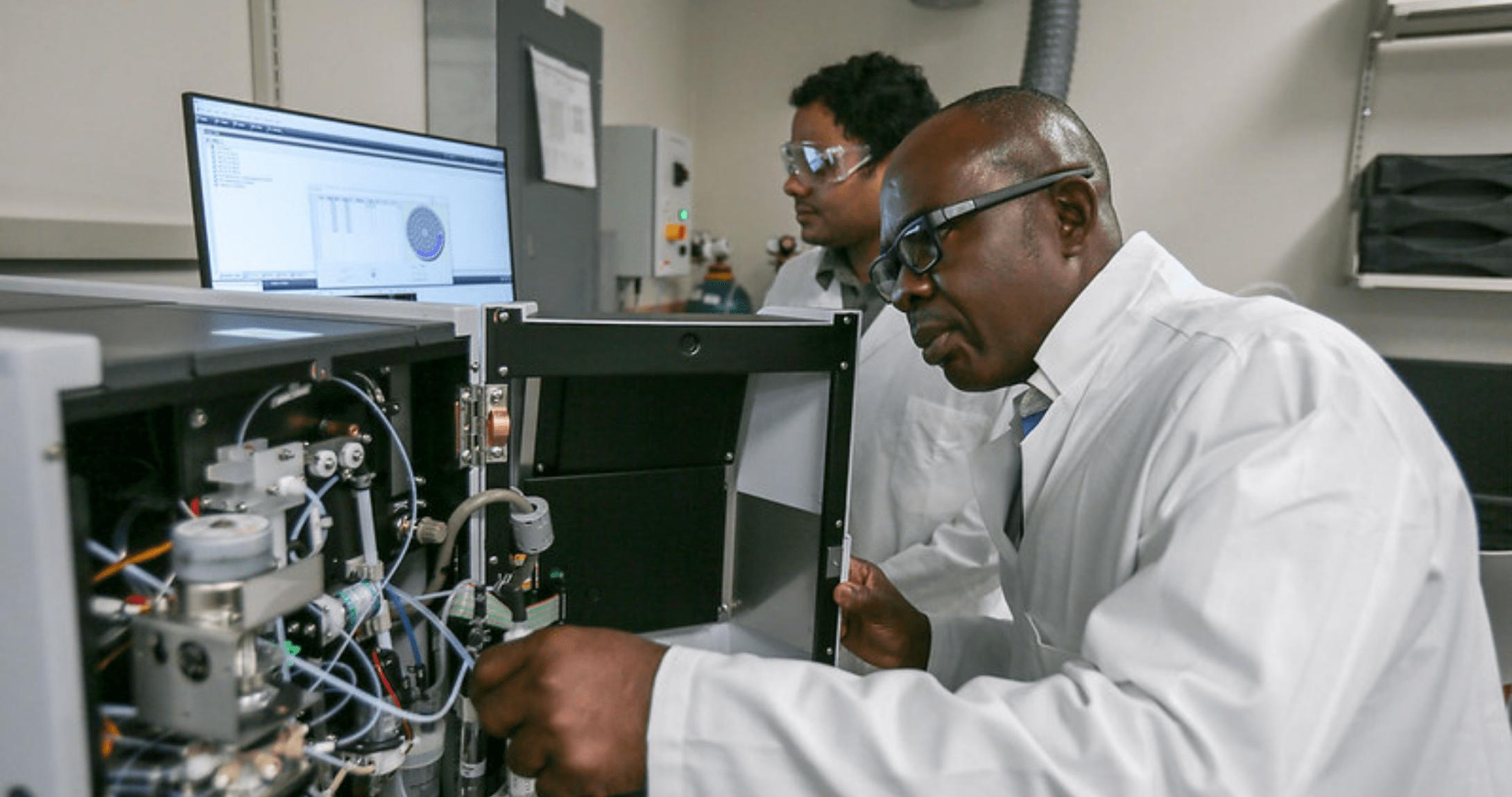 Dos profesores de ingeniería en el laboratorio mirando la máquina