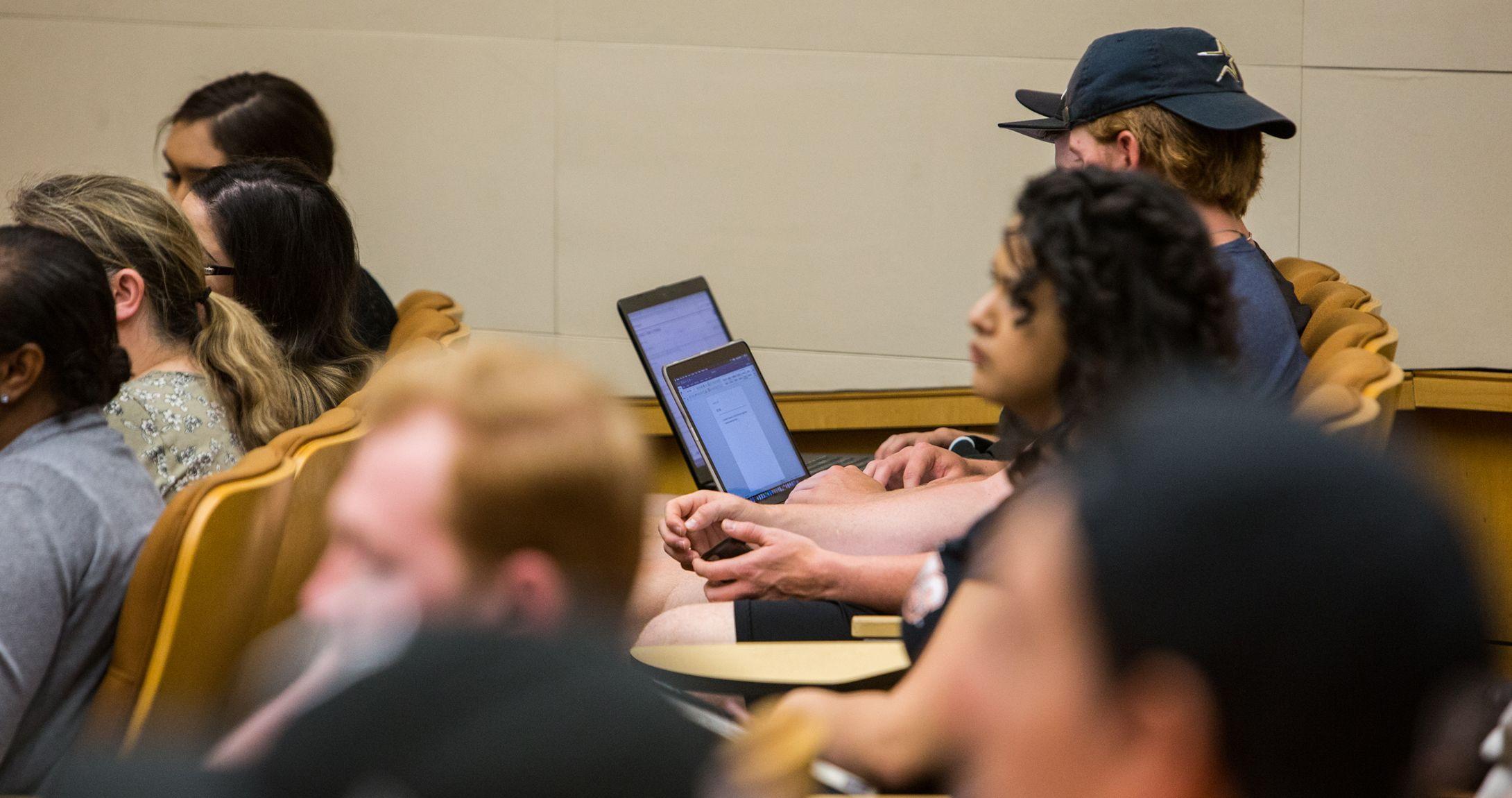 Estudiantes sentados en sus escritorios en un auditorio.