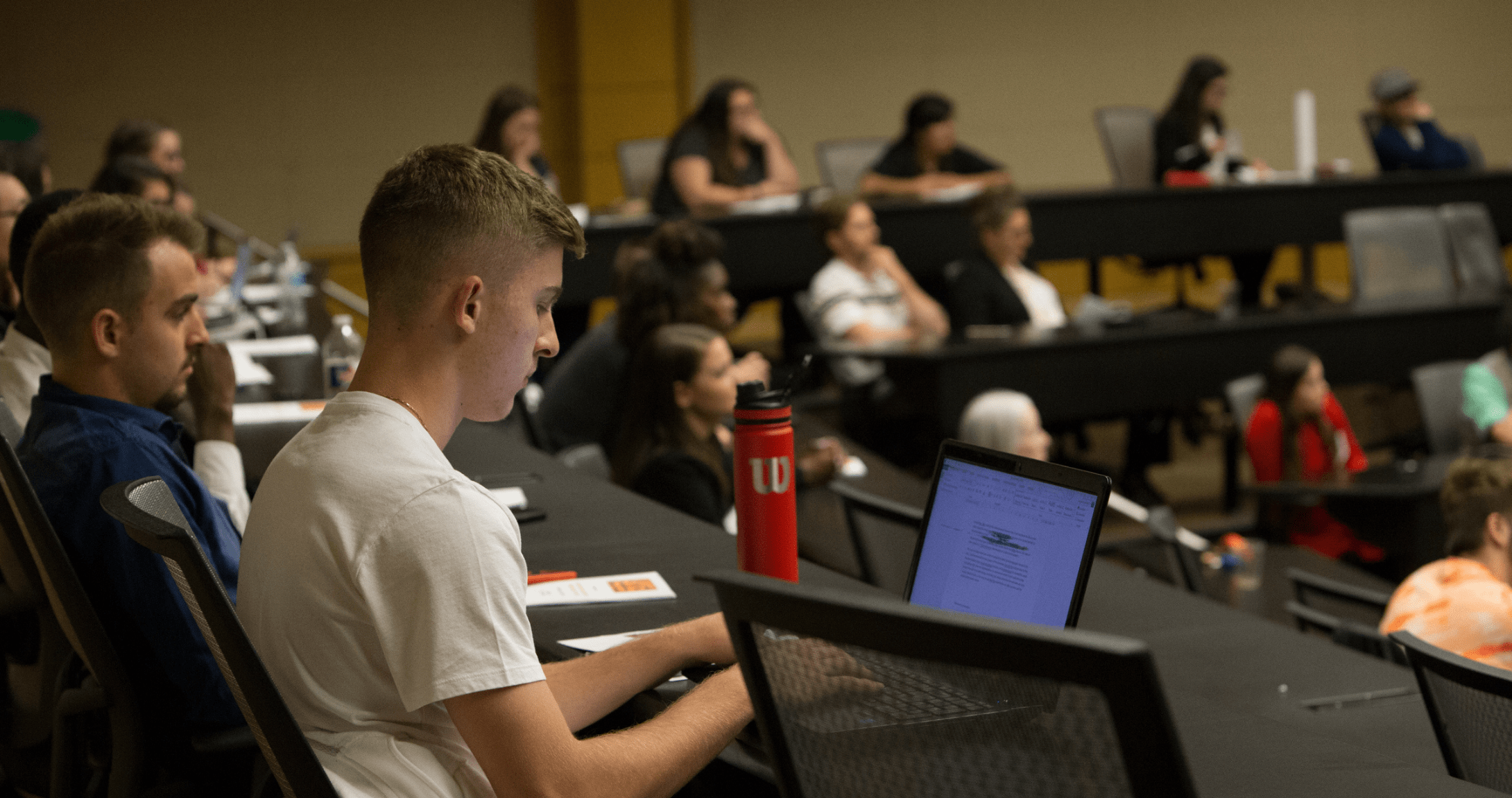 student on computer in lecture hall