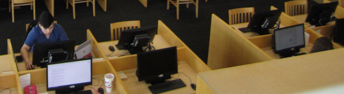 estudiantes que usan computadoras en la biblioteca.