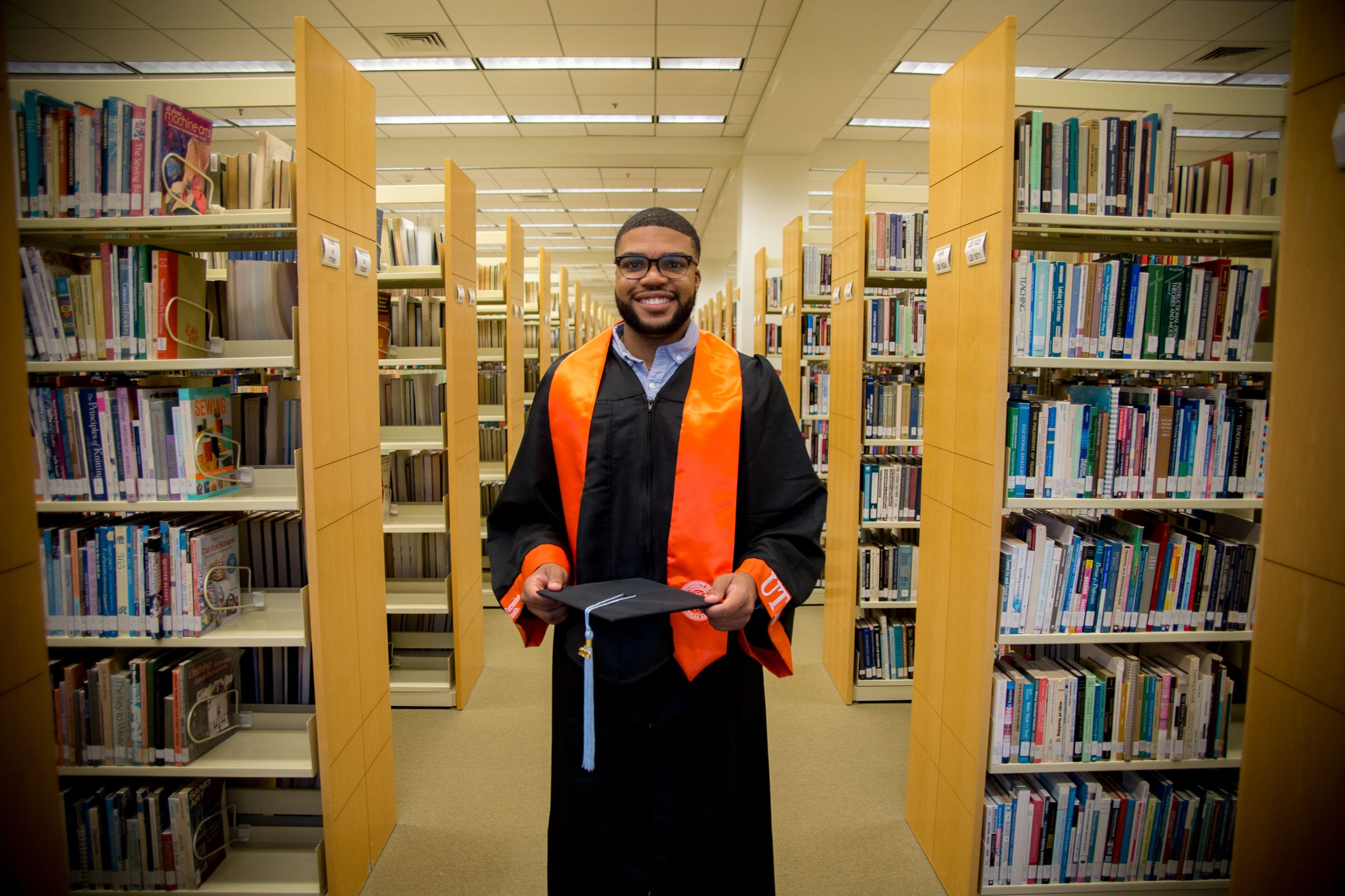 Student holding graduation cap in library